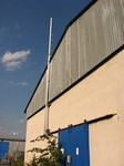 Trubkový stožárek 9 m umístěný na štítové sťěně budovy